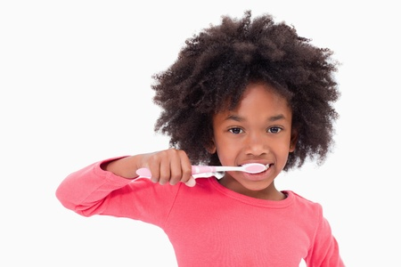 Girl brushing her teeth against a white background Stock Photo