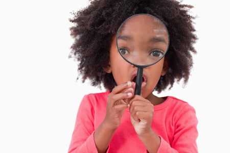 Girl looking through a magnifying glass against a white background photo