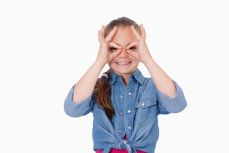 Girl with her fingers around her eyes against a white background photo