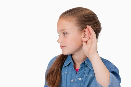 Cute girl pricking up her ear against a white background photo