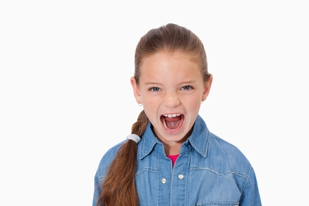 Unhappy girl screaming against a white background photo
