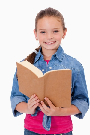 Portrait of a smart girl reading a book against a white background photo