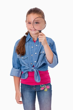 Portrait of a girl looking through a magnifying glass against a white background photo