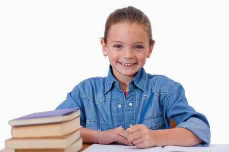 Smiling girl writing on a notebook against a white background photo