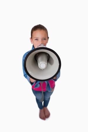 Portrait of a girl speaking through a megaphone against a white background photo