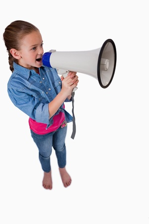 Portrait of a cute girl speaking through a megaphone against a white background photo