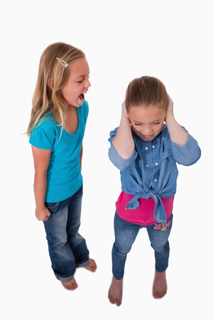 Portrait of a girl screaming at her friend against a white background photo