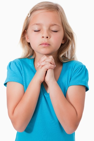 Portrait of a young girl praying against a white background photo