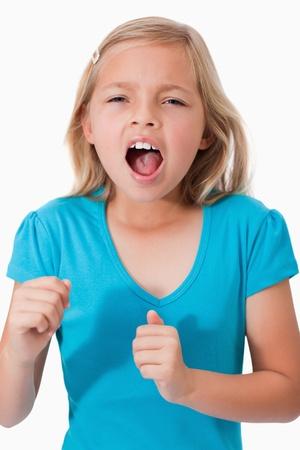 facial gestures: Retrato de una joven gritando contra un fondo blanco