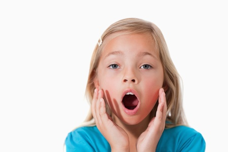 mouth  open: Young girl being scared against a white background Stock Photo