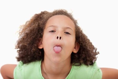 lengua afuera: Linda chica sacando la lengua contra un fondo blanco
