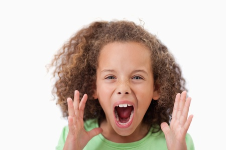 Angry girl screaming against a white background photo