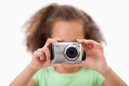 Little girl taking a picture against a white background photo