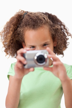Portrait of a girl taking a picture against a white background photo