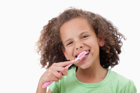 Smiling girl brushing her teeth against a white background photo