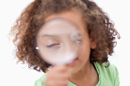 Cute girl looking through a magnifying glass against a white background photo