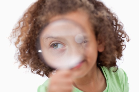 Smiling girl looking through a magnifying glass against a white background photo