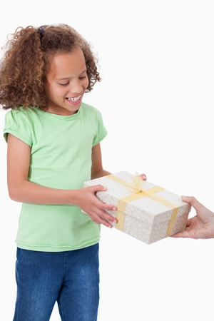 Portrait of a young girl receiving a present against a white background photo