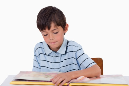 Boy reading a book against a white background photo