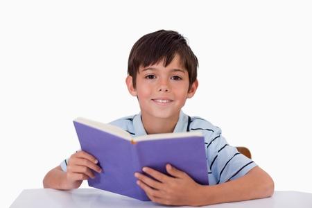 niños estudiando: Niño feliz leyendo un libro sobre un fondo blanco