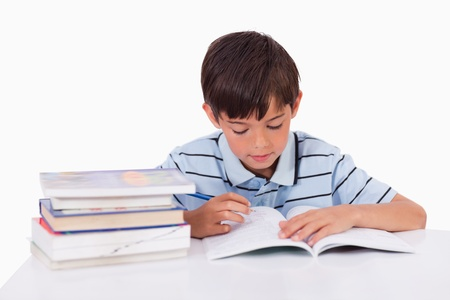 Boy learning his lessons against a white background photo