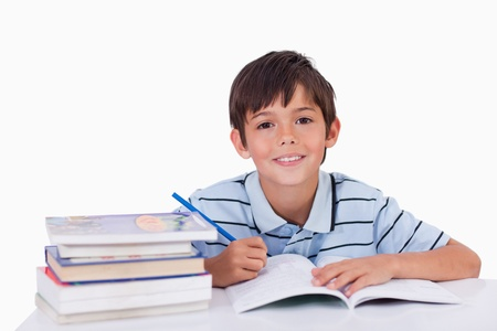 Boy doing his homework against a white background photo