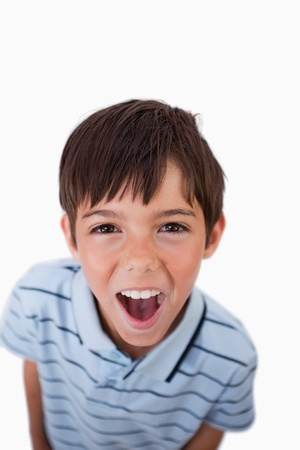 Portrait of a boy screaming at the viewer against a white background photo