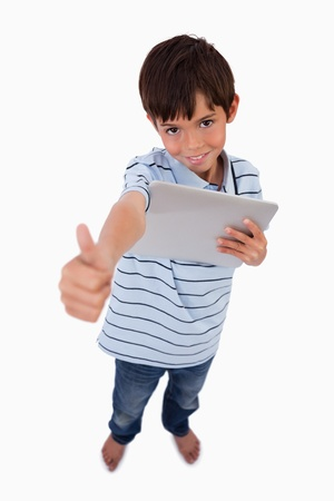 Portrait of a boy using a tablet computer with the thumb up against a white background photo