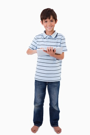 Portrait of a cute smiling boy using a tablet computer against a white background photo