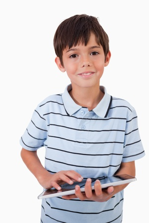 Portrait of a cute little boy using a tablet computer against a white background photo
