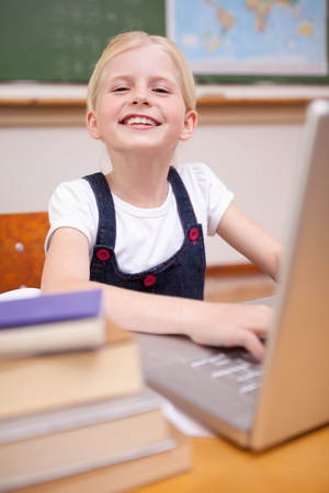 Portrait of a girl using a notebook in a classroom photo