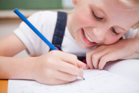 kids writing: Close up of a schoolgirl writing something in a classroom Stock Photo