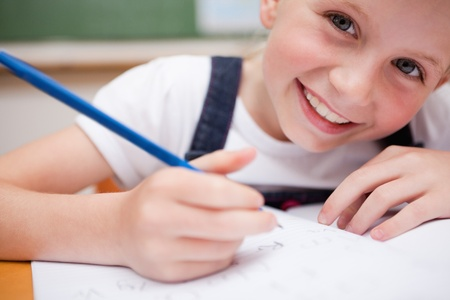 Close up of a smiling schoolgirl writing something in a classroom Stock Photo - 11684765