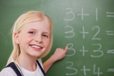 Blonde schoolgirl pointing at something on a blackboard photo