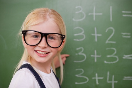 brainy: Smiling smart schoolgirl pointing at something on a blackboard