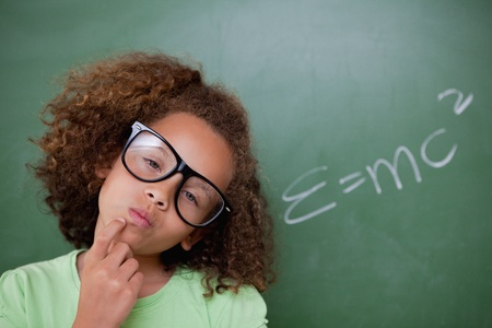 Smart schoolgirl thinking in front of a blackboard photo