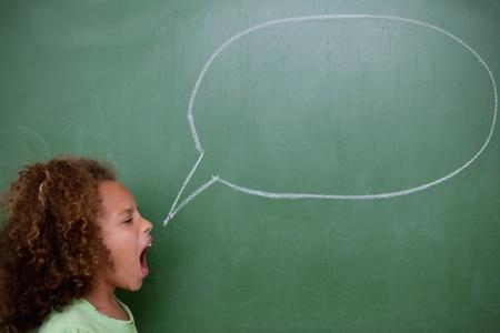 Schoolgirl screaming a speech bubble in front of a blackboard Stock Photo - 11679597