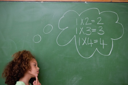 Schoolgirl thinking about algebra in front of a blackboard photo