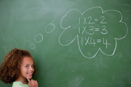 Schoolgirl thinking about mathematics in front of a blackboard photo