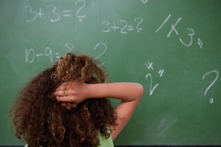 Schoolgirl thinking about mathematics while scratching the back of her head in front of a blackboard photo