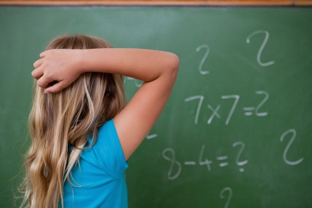 scratching: Little schoolgirl thinking while scratching the back of her head in front of a blackboard Stock Photo