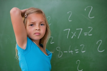 Schoolgirl thinking while scratching the back of her head in front of a blackboard photo