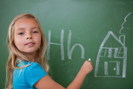 Schoolgirl learning the alphabet on a blackboard photo