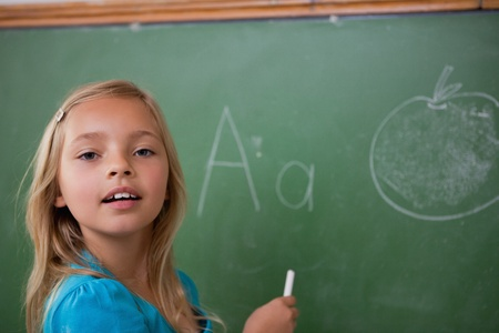 Young schoolgirl learning the alphabet on a blackboard photo