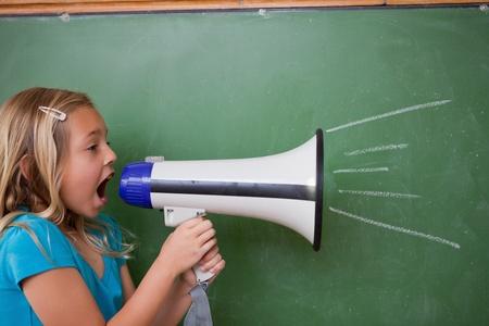 niÑos hablando: Colegiala joven gritando con un megáfono delante de la pizarra