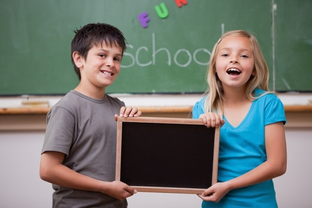 Happy pupils holding a school slate in a classroom Stock Photo - 11679765