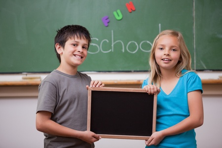 Smiling pupils holding a school slate in a classroom photo