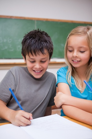 preteens girl: Portrait of happy pupils working together in a classroom Stock Photo