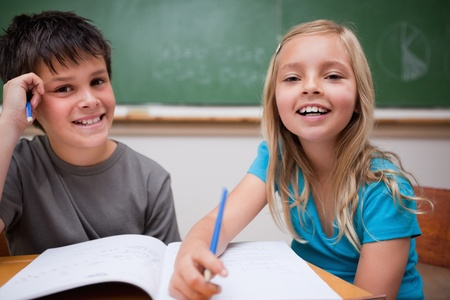 Two children writing in a classroom photo