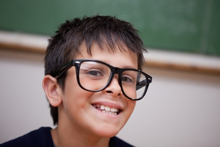 Close up of a smiling schoolboy in a classroom photo